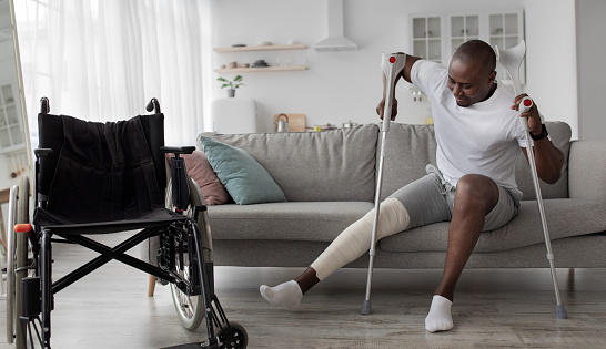 Patient is recuperating in living room due to illness. Concentrated cheerful tense adult african american guy with broken leg in cast stands up with crutches from couch near wheelchair, panorama