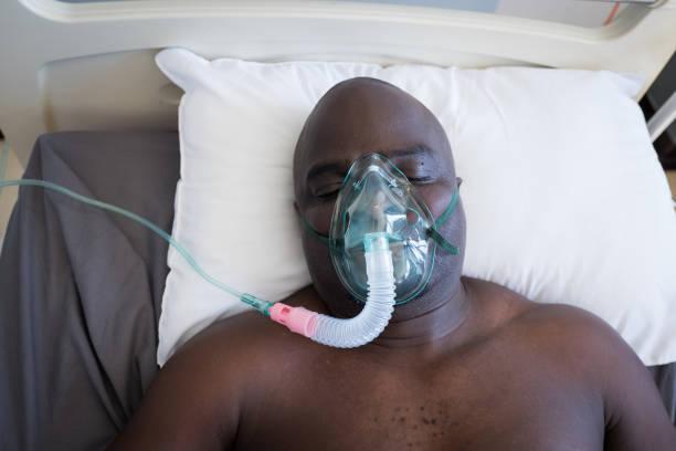 patiënt ligt in ziekenhuisbed op een gasmasker - ventilator bed stockfoto's en -beelden