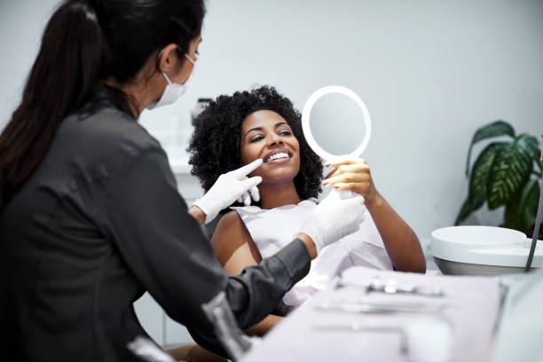 Patient schaut Zähne im Spiegel in Zahnklinik – Foto