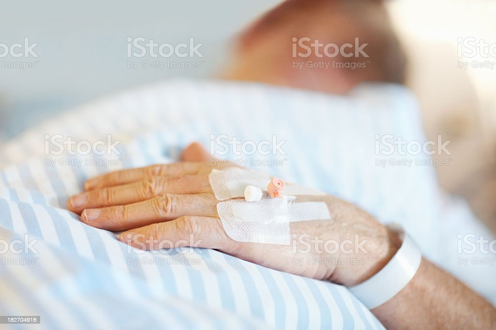 Patient lying on bed with IV drip inserted in hand royalty-free stock photo