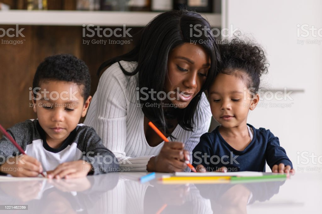 A patient mother homeschool during a pandemic A mother helps her children with their lessons as she homeschool them during the pandemic. Both mixed race children of elementary school age are colouring in and seated at the kitchen island. Adult Stock Photo