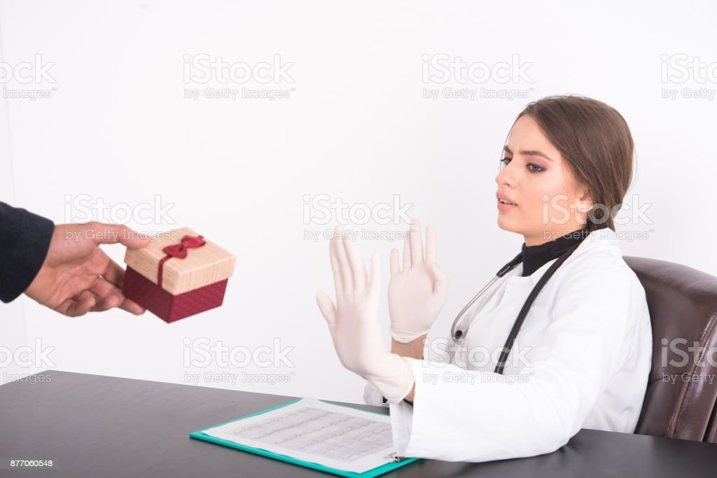 Patient offering a gift to a doctor which she refuses stock photo