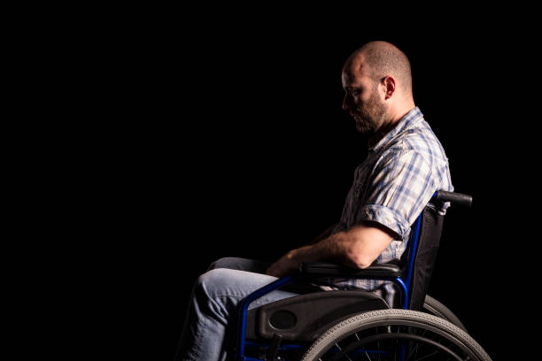 patient on wheelschair Portrait of caucasian man sitting in a wheelchair, sad and thoughtful expression. Black background. Concept of patient and physical disability. paraplegic stock pictures, royalty-free photos & images