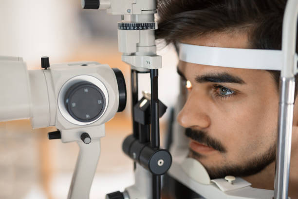 Patient or customer at slit lamp at optometrist or optician stock photo