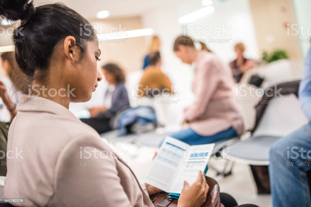 Patient reading brochure stock photo