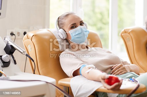 Portrait of young woman in protective mask looking at camera while lying on the couch and receiving a blood transfusion at hospital