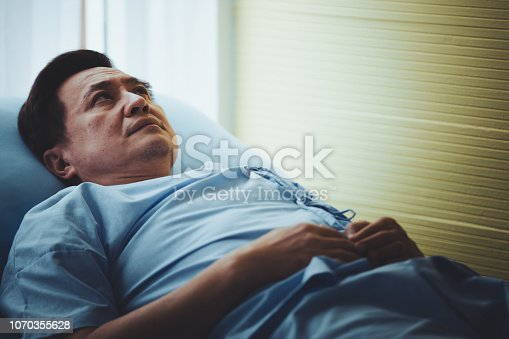 941439642 istock photo Patient senior man lying on bed resting tired looking sad 1070355628