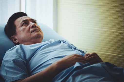 1049772134 istock photo Patient senior man lying on bed resting tired looking sad 1070355628