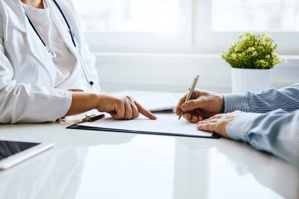 Patient signs a document with his doctor stock photo