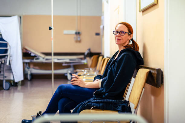 Patient sitting in hospital ward hallway waiting room with iv. Patient sitting in hospital ward hallway waiting room with iv. Woman with intravenous therapy in her hand is waiting in the clinic corridor with blurred medical personnel in background. chemotherapy cancer stock pictures, royalty-free photos & images