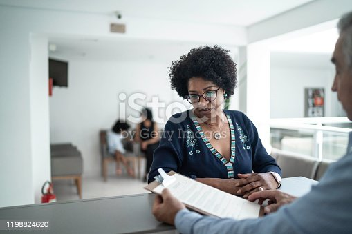 istock Patient talking to the secretary at hospital reception 1198824620