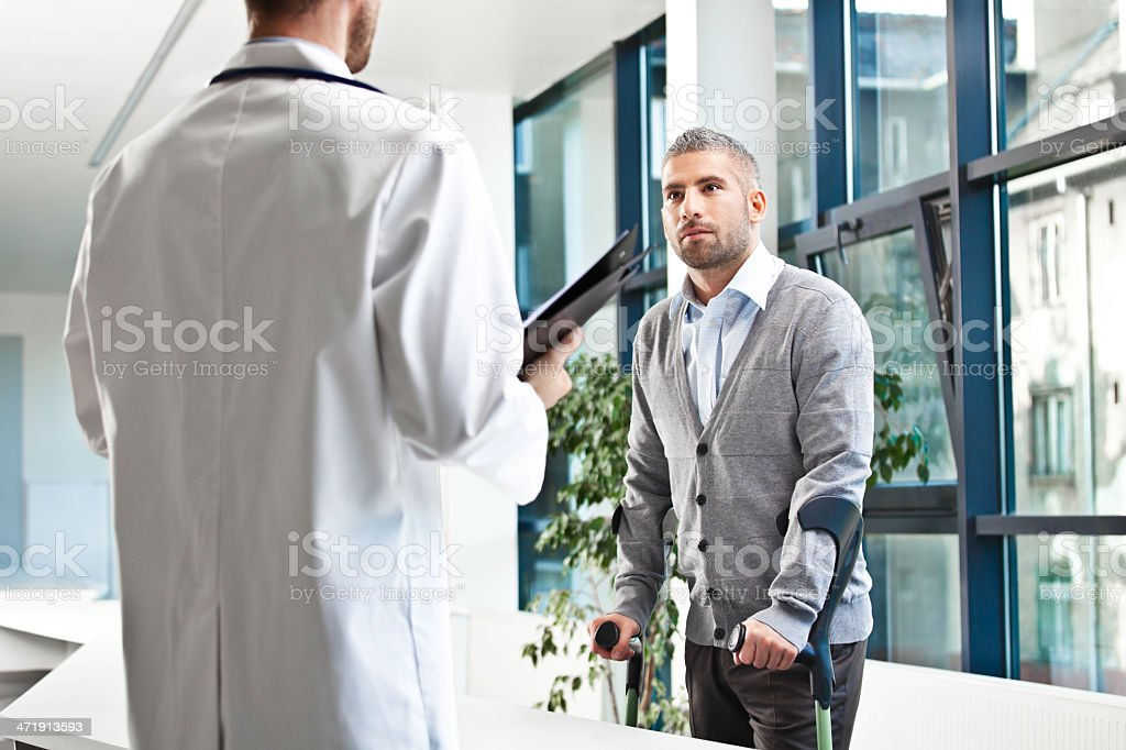 Patient talking with male doctor stock photo