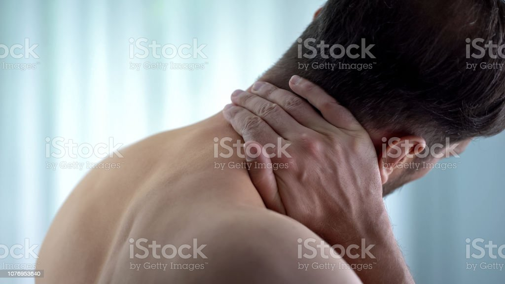 Patient touching neck, feeling spasm upper back, pinched nerve,...