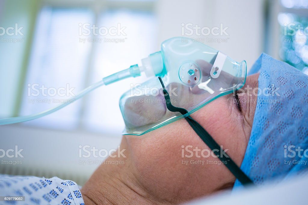 Patient wearing oxygen mask lying on hospital bed stock photo