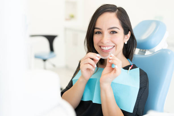 Patient With Clear Aligner At Clinic Smiling beautiful Caucasian mid adult woman holding invisible orthodontic retainer dental health stock pictures, royalty-free photos & images