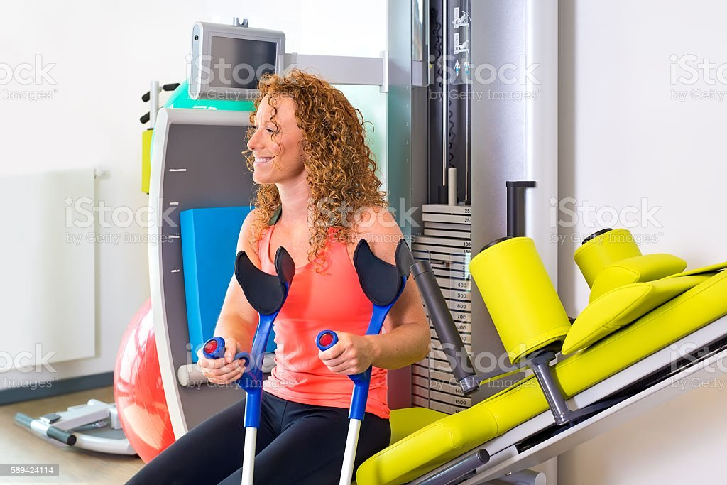Patient with crutches sitting on weight machine. stock photo