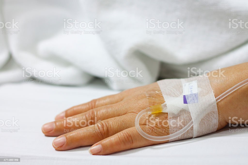 Patient with IV medication needle on hand stock photo