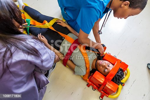 Patient with spinal injuries being examined by doctors while in a neck brace