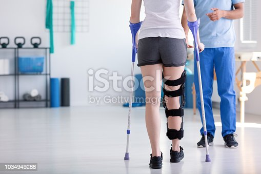 Patient with stiffener on the leg walking with crutches during rehabilitation