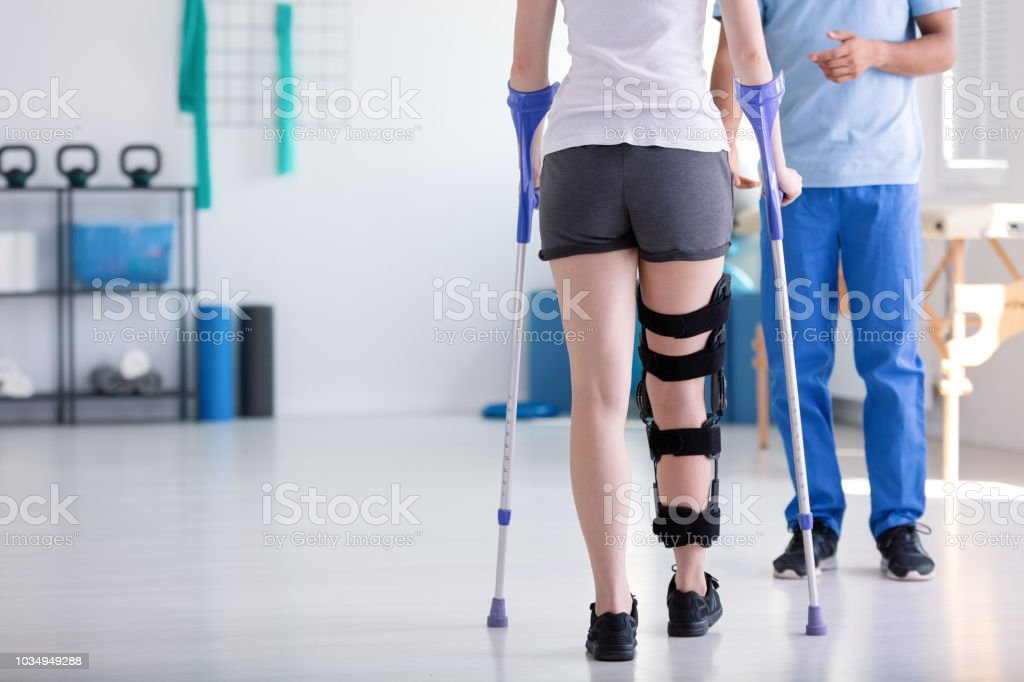 Patient with stiffener on the leg walking with crutches during rehabilitation stock photo