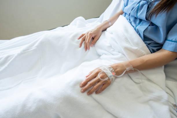 geduldige vrouw die met het ontvangen van intraveneuze vloeistof direct in een ader slaapt. - infuusoplossing stockfoto's en -beelden