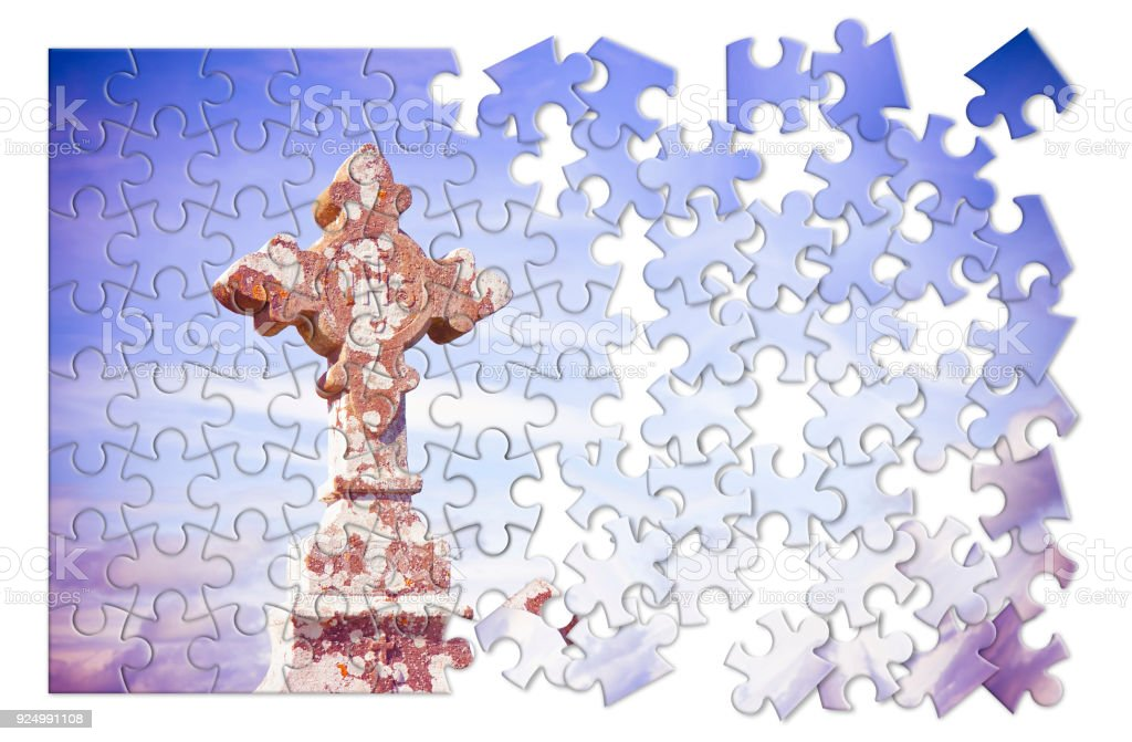 Patiently building of faith - Celtic carved stone cross against a sky background - concept image in puzzle shape stock photo