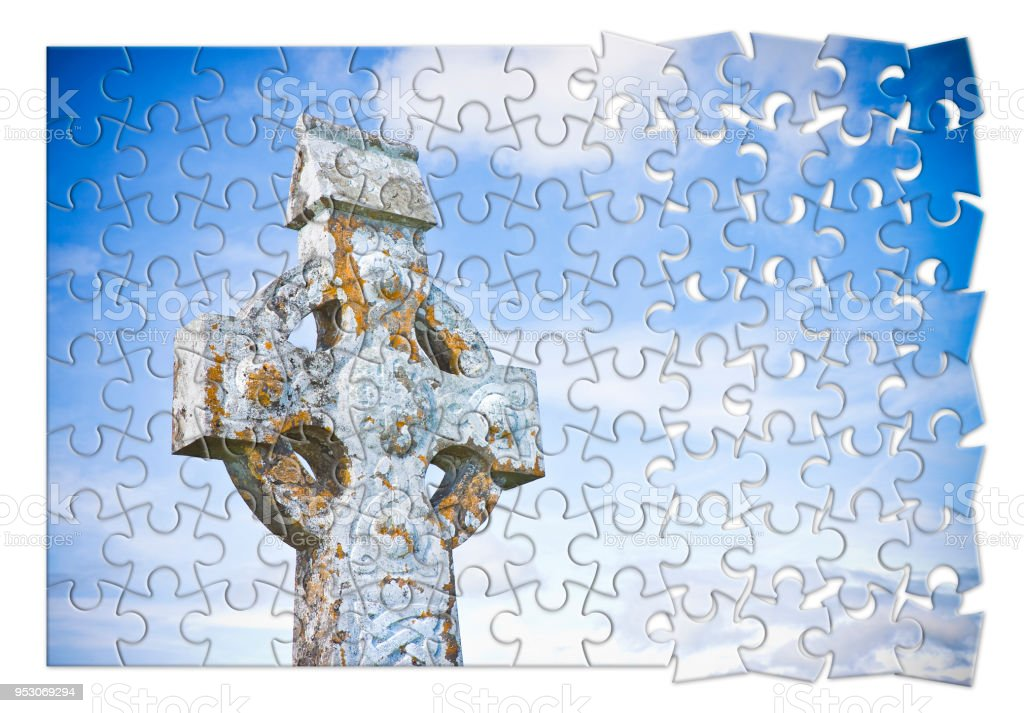 Patiently building of faith - Celtic carved stone cross against a sky background - concept image in jigsaw puzzle shape stock photo
