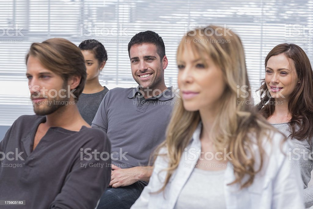 Patients listening in group therapy with one man smiling royalty-free stock photo