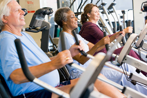 Patients Working Out In Gym Patients Working Out In Gym Looking Ahead Smiling exercise machine stock pictures, royalty-free photos & images