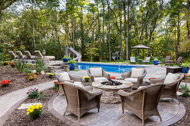 Patio Fire Pit by Swimming Pool Fire pit next to the swimming pool in the evening sun. backyard pool stock pictures, royalty-free photos & images