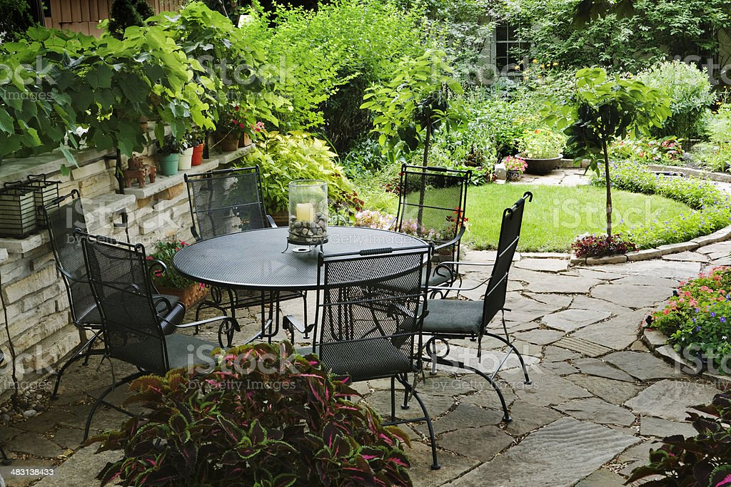 A quiet patio with table and chairs furniture in a back yard garden...