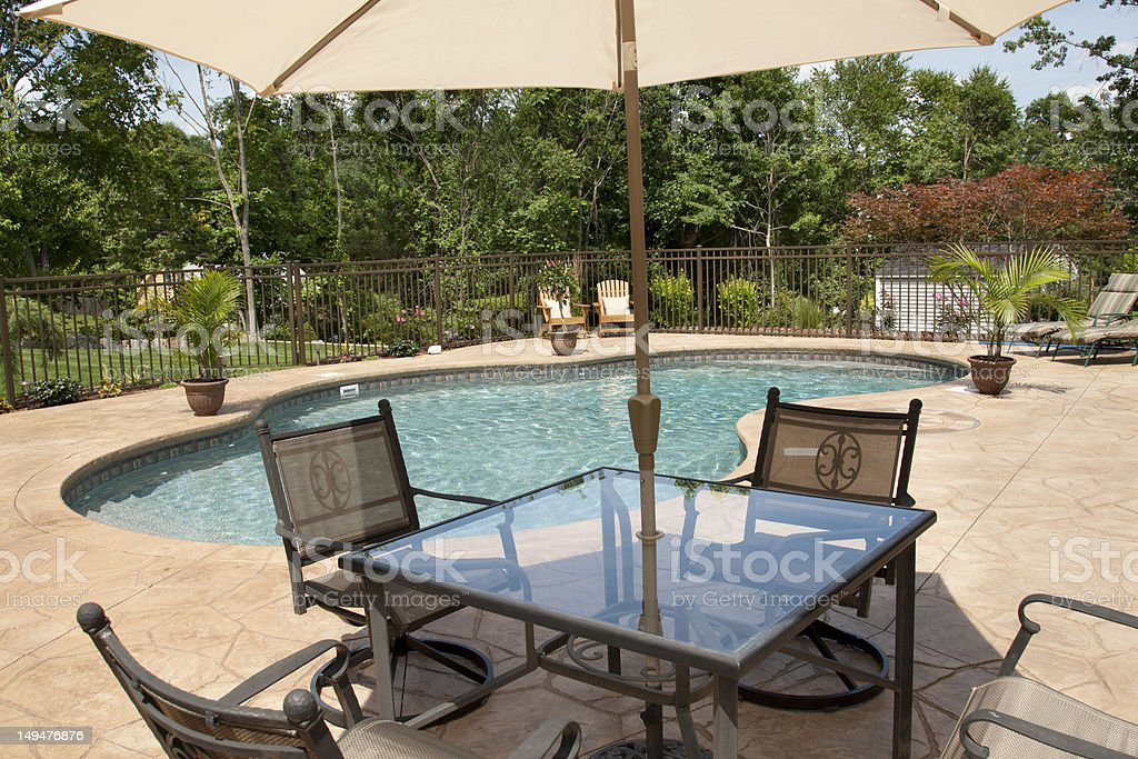 Patio furniture overlooking lush salt water pool. stock photo