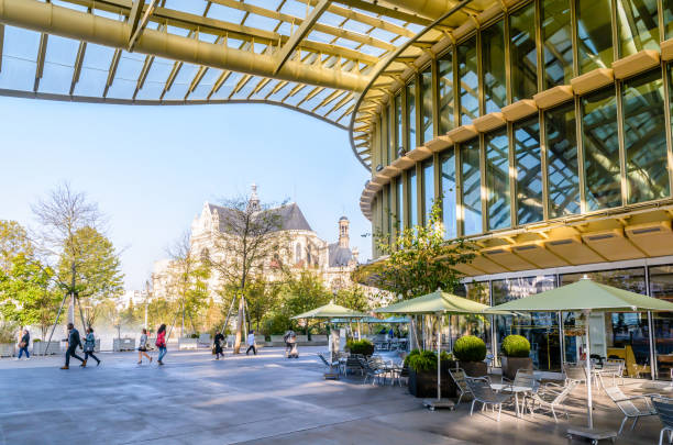 patio of the forum des halles underground shopping mall in the center of paris, covered by a vast glass canopy, with church of saint-eustache in the background. - saint eustache church foto e immagini stock