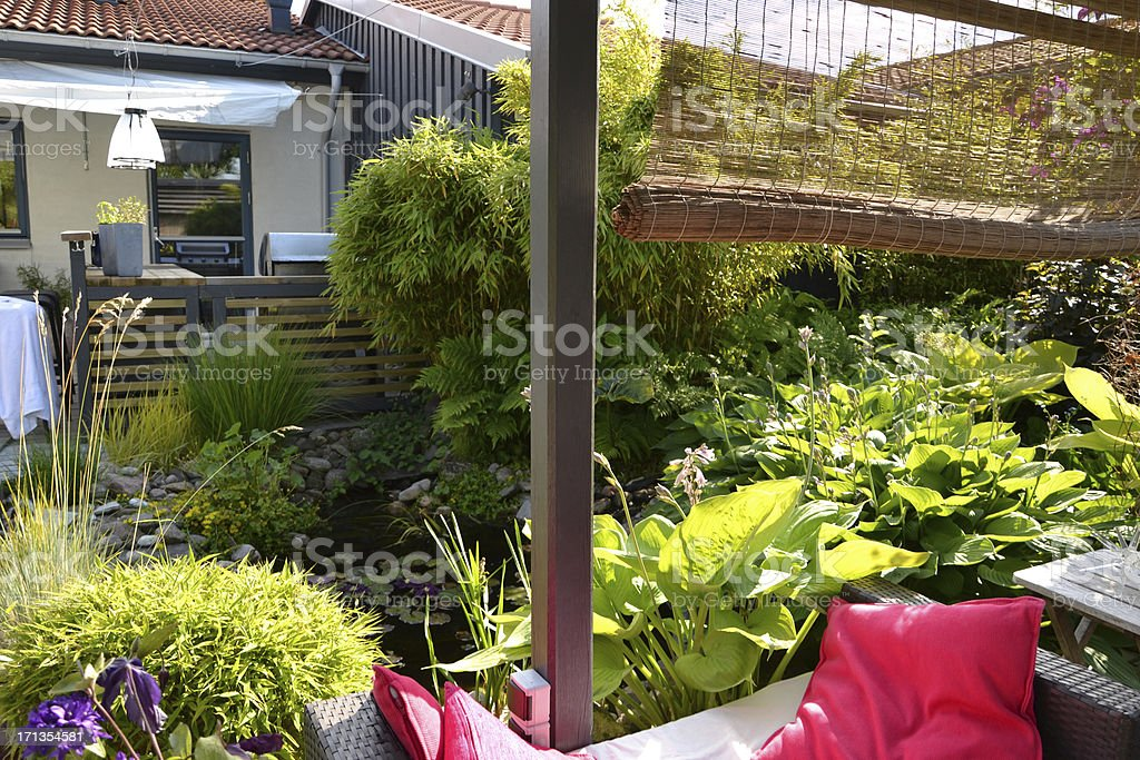 Patio, Outdoor Kitchen And A Pond In The Afternoon Sun Stock Photo