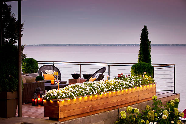 terrasse mit blick über den see bei sonnenuntergang. - terrassen lichterketten stock-fotos und bilder