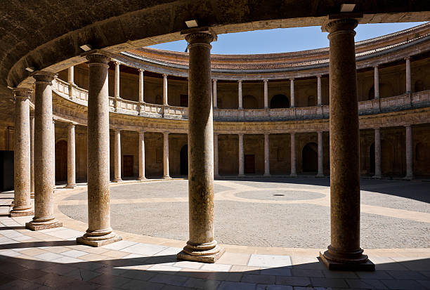 Patio Palace Of Charles V in Alhambra, Granada The palace was designed by Pedro Machuca and built in 1527. The circular patio has two levels. The lower consists of a doric colonnade of conglomerate stone, with an orthodox classical entablature formed of triglyphs and metopes. The upper floor is formed by a stylized ionic colonnade whose entablature has no decoration. palace of charles v stock pictures, royalty-free photos & images