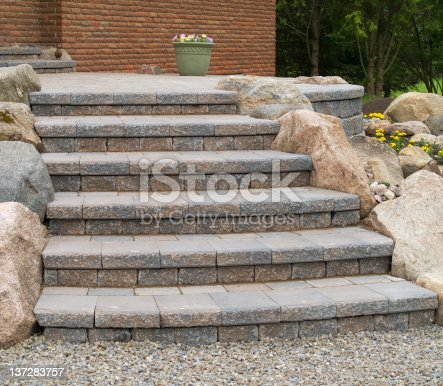 Details of stone steps leading from a patio.