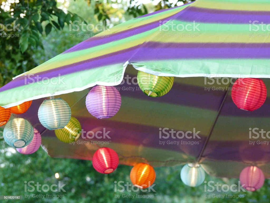 Patio Umbrella with glowing chinese paper lantern string lights stock photo