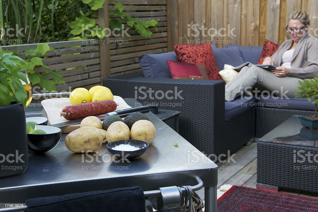 Patio with an Outdoor kitchen. Woman relaxing stock photo