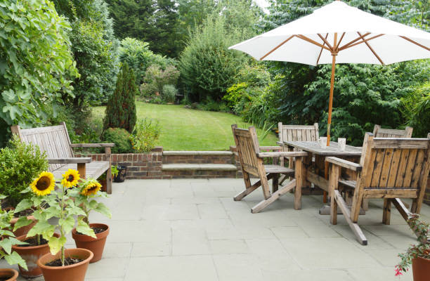 Patio with garden furniture and parasol London garden in summer with patio, wooden garden furniture and a parasol or sun umbrella lawn stock pictures, royalty-free photos & images