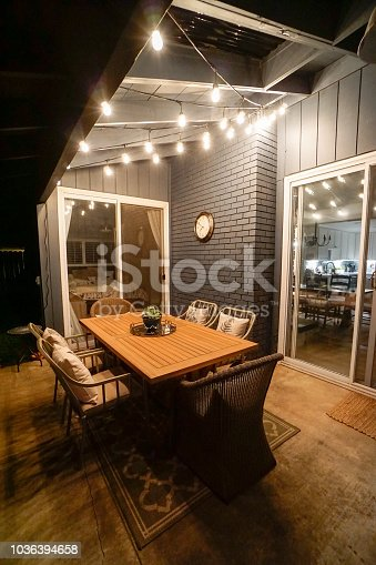 Equipped cozy veranda of house with wooden table and chairs illuminated by ceiling lamps in darkness of night