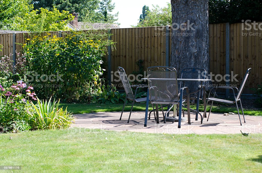 Patio with table and chairs in garden – Foto