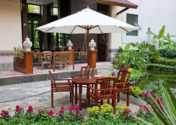terrasse mit tisch und stühlen - sonnenschirm terrasse stock-fotos und bilder