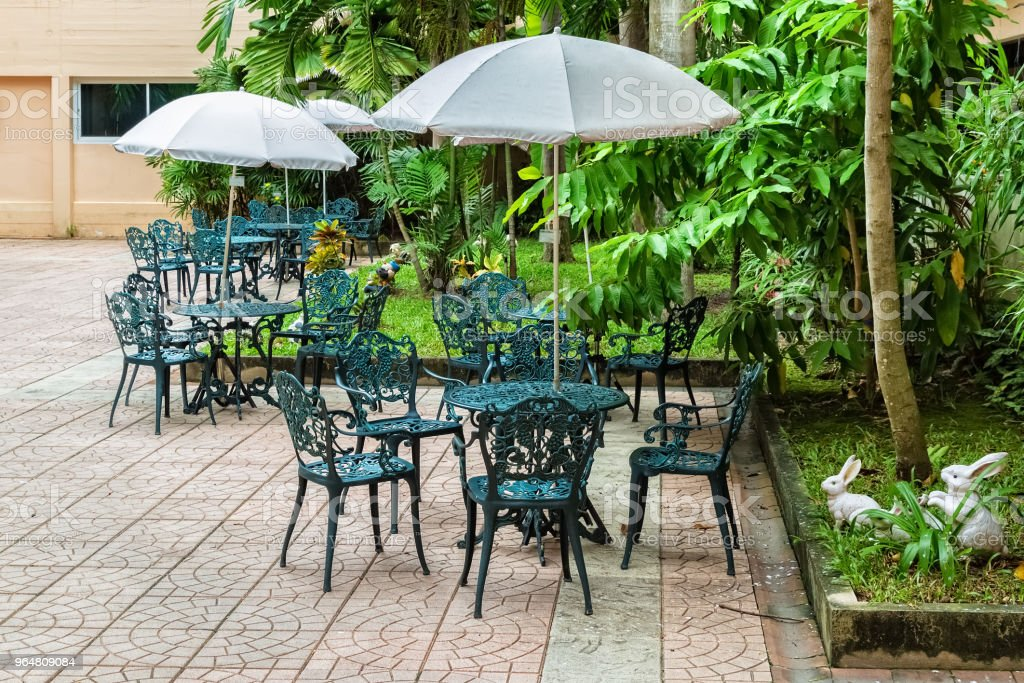 Patio with Tables and Alloy chairs under Umbrella in Garden royalty-free stock photo