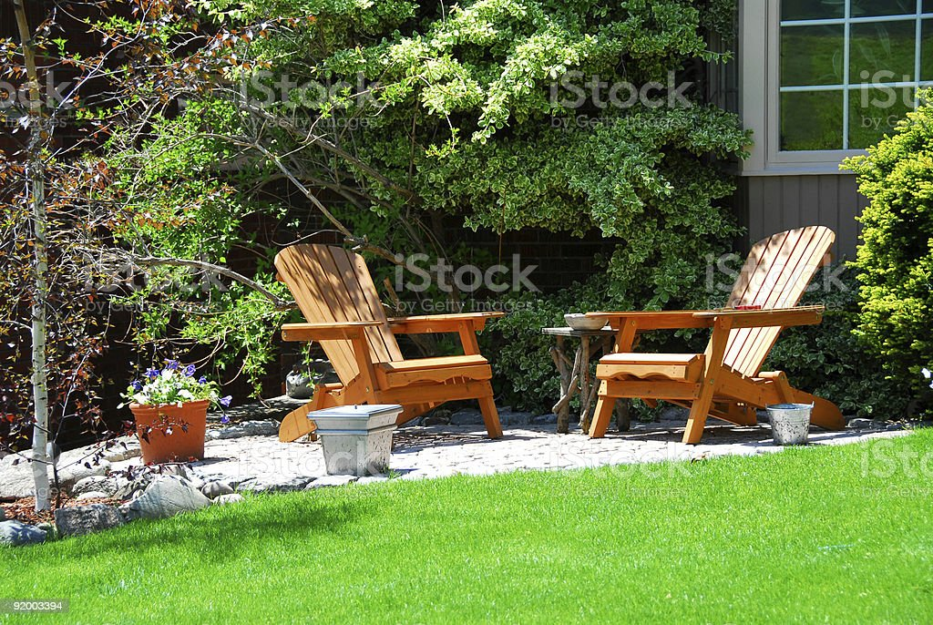 A patio with two wooden chairs outside a house stock photo