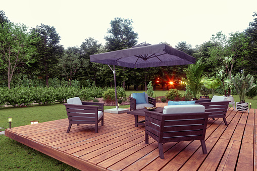 Patio With Wooden Seats, Coffee Table And Sunshade In The Garden with Sunset View Background.