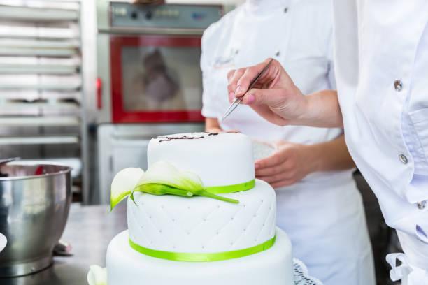 patissier verzieren große torte zum geburtstag - hausgemachte hochzeitstorten stock-fotos und bilder