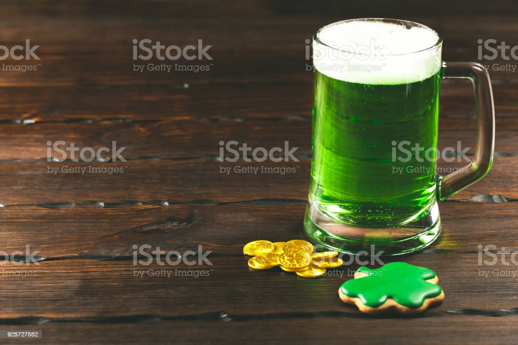 Patrick's day background with a Glass of green beer and clover gingerbread with gold coins on wooden background stock photo