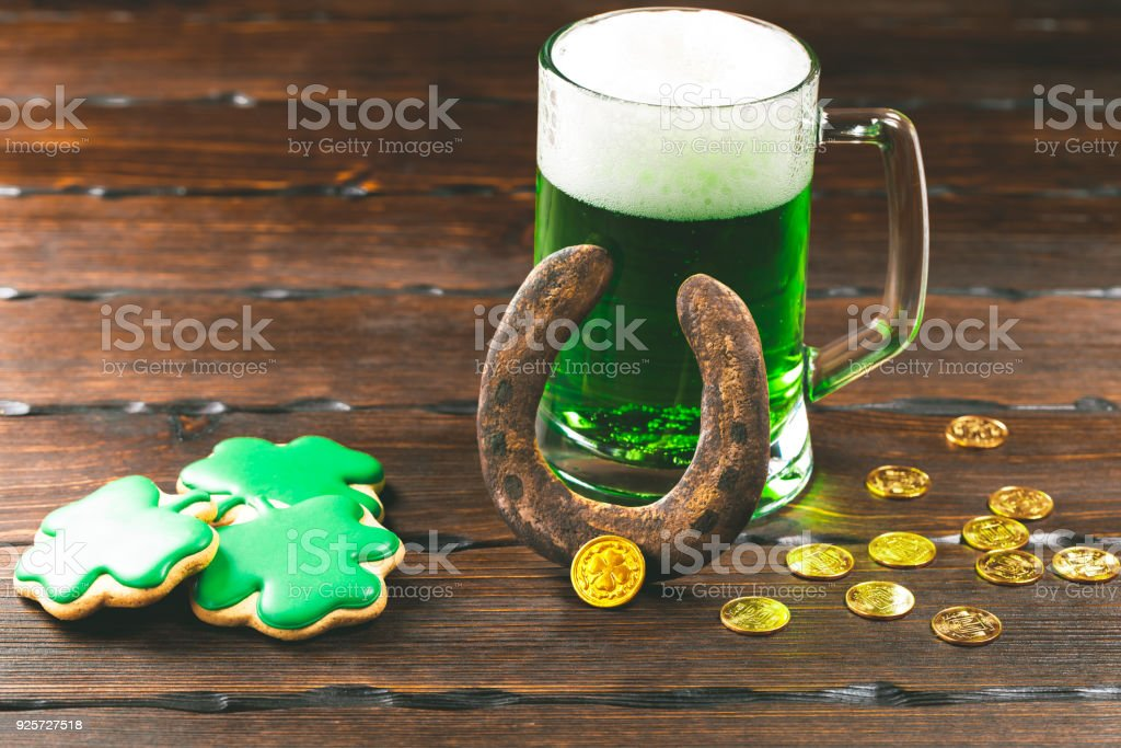 Patrick's day background with a Glass of green beer, clover and and horseshoe gingerbread with gold coins on wooden background stock photo