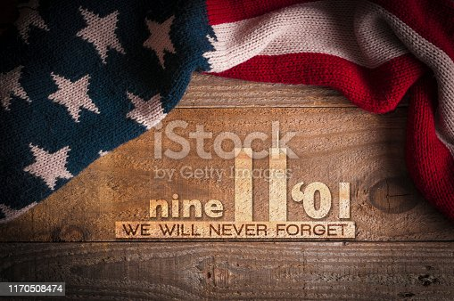 istock Patriot day 2019: A scarf with the colors of the American flag on a wooden table and an inscription in memory of September 11th 1170508474